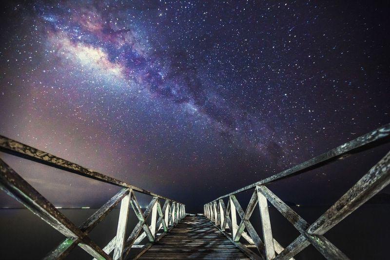 Footbridge against milky way at night