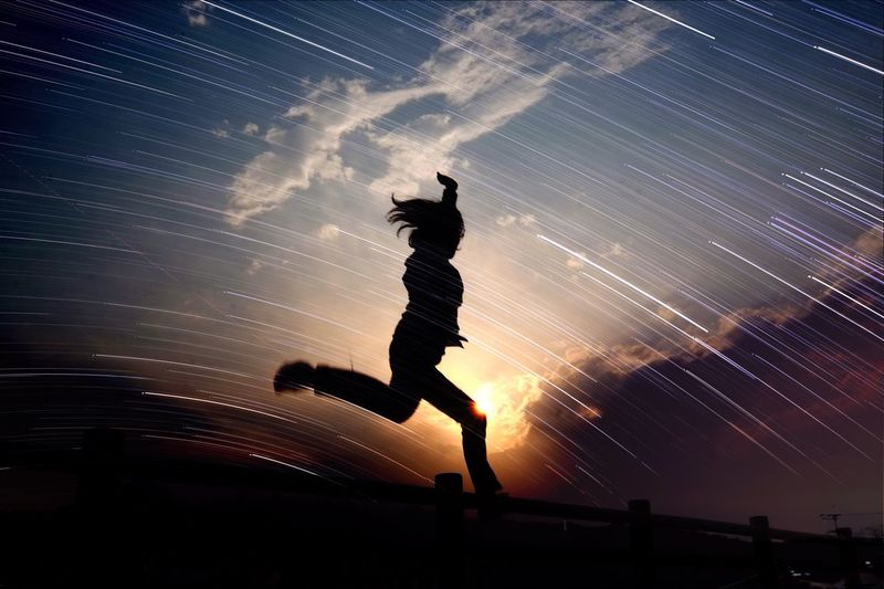 Low angle view of woman dancing against clear sky