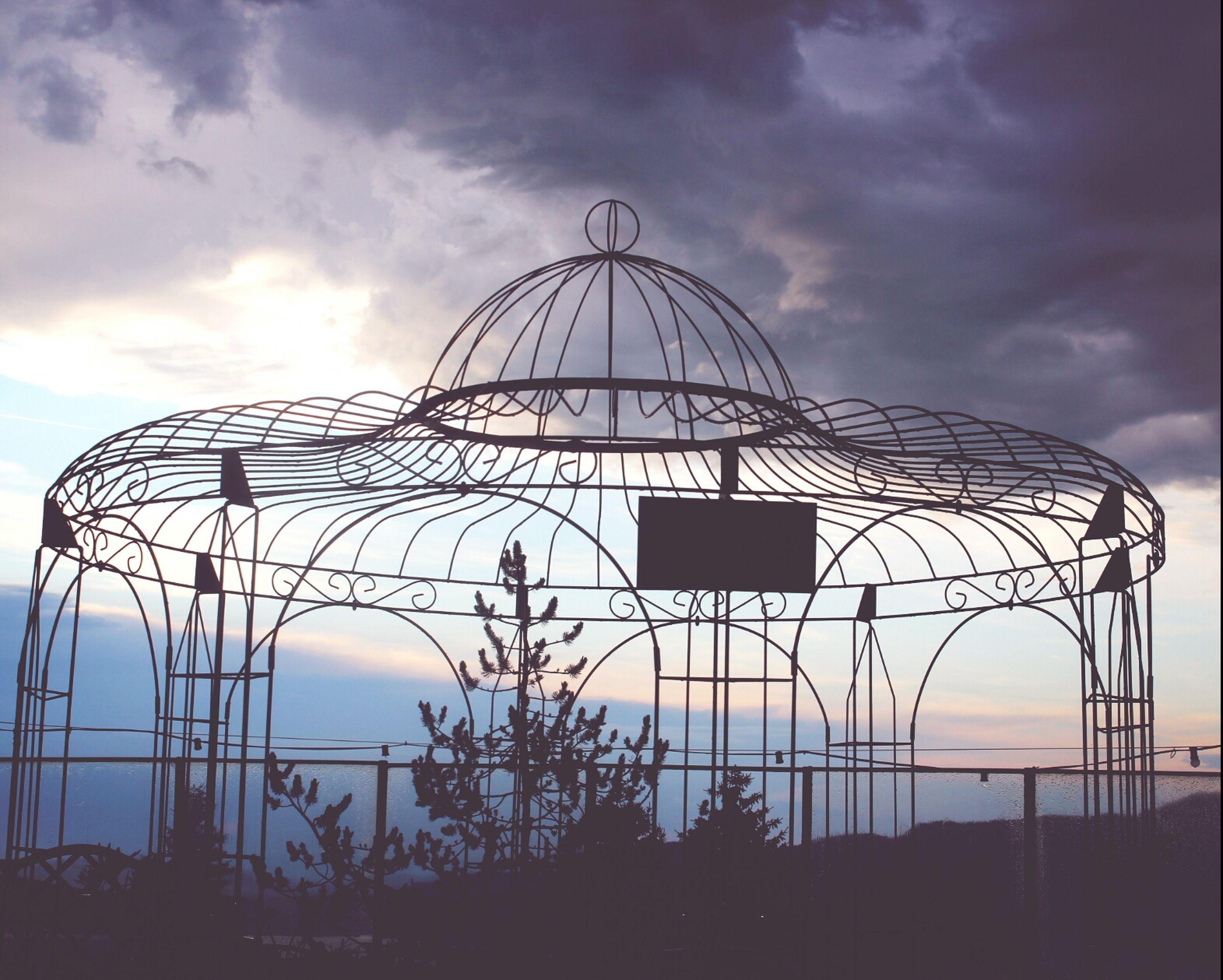sky, low angle view, cloud - sky, cloudy, built structure, silhouette, cloud, amusement park, ferris wheel, amusement park ride, architecture, arts culture and entertainment, sunset, lighting equipment, dusk, outdoors, circle, no people, metal, building exterior