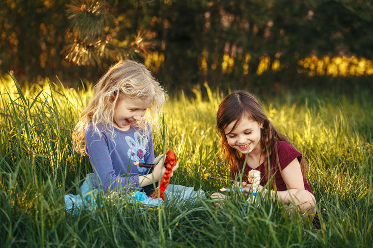 Happy children girls playing dolls in park.  kids sitting in grass on meadow playing toys