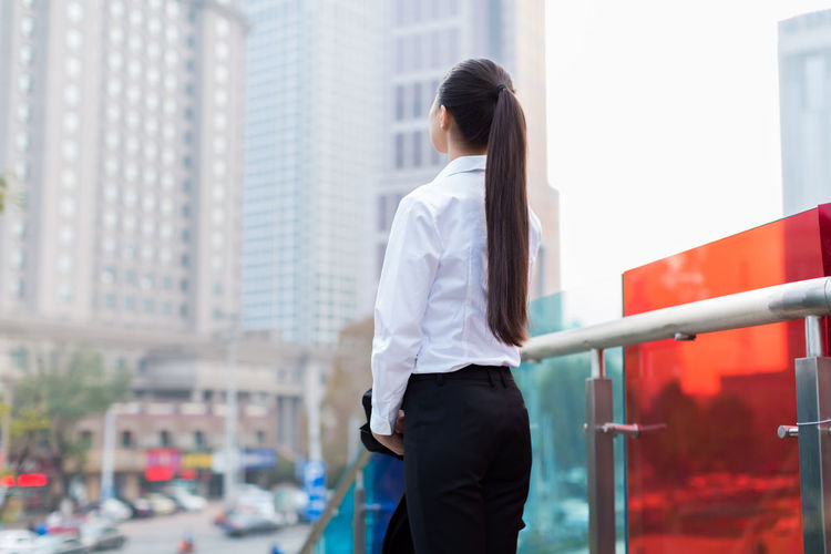 Thoughtful young businesswoman standing by railing in city