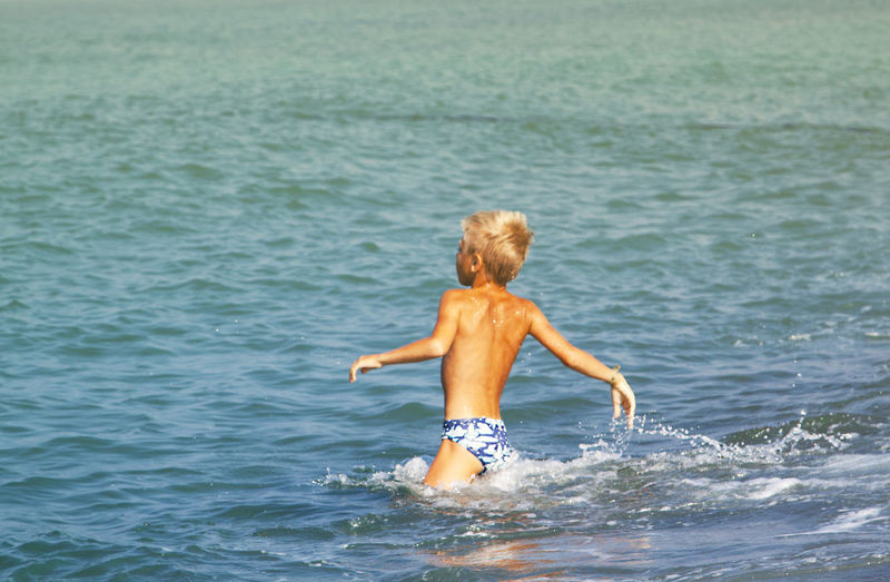 Rear view of shirtless boy swimming in sea against clear sky