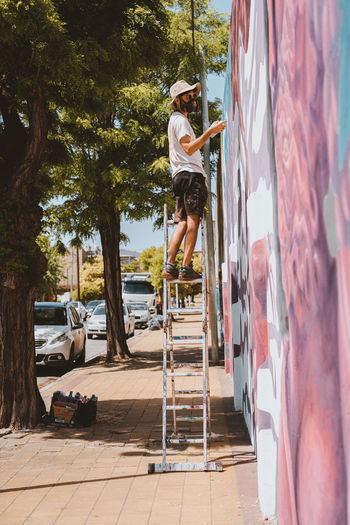 Man on wall against trees