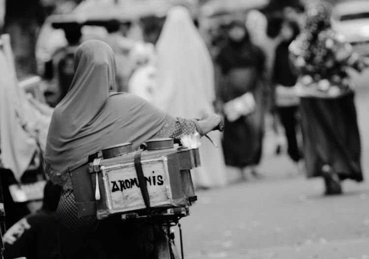 Rear view of woman with bicycle selling food on street