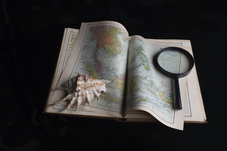 Map Black Background Studio Shot Indoors  No People High Angle View World Map Directly Above Direction Still Life Close-up Guidance Paper Publication Travel Book Group Of Objects Water Exploration Shell Magnifier Travel Geography