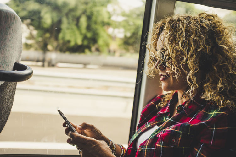 Woman using mobile phone by window in bus