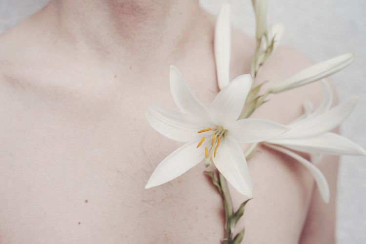 Midsection of shirtless man with flowers