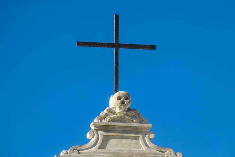 Low Angle View Of Skull On Cross Against Clear Blue Sky