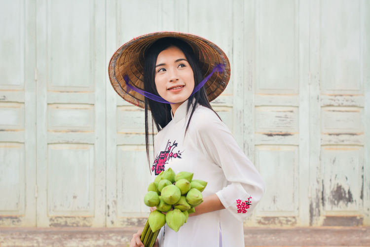 Beautiful woman wearing conical hat standing holding lotus buds