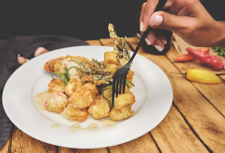 Midsection of person holding food in plate on table