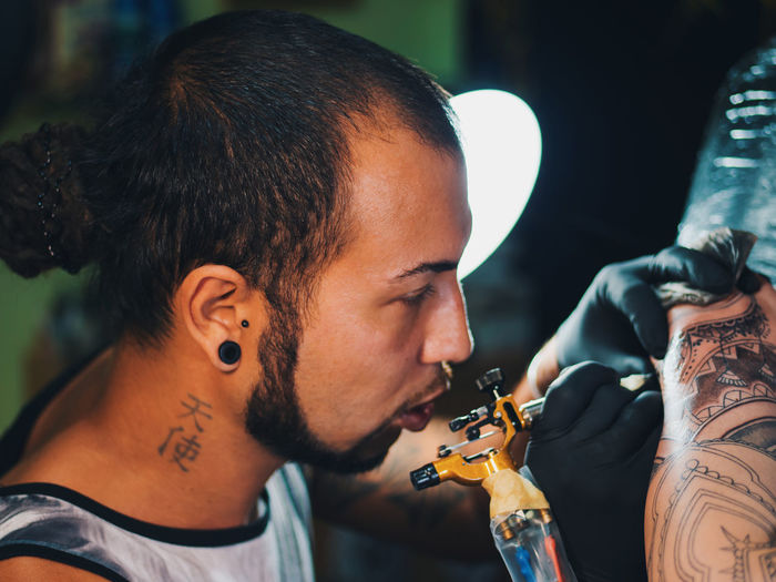 Man Tattooing On Hand