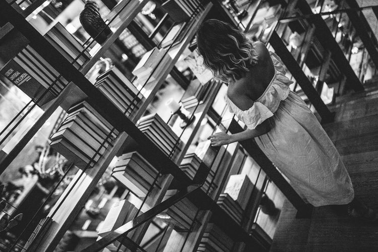 High Angle View Of Woman Standing At Bookshelf In Library