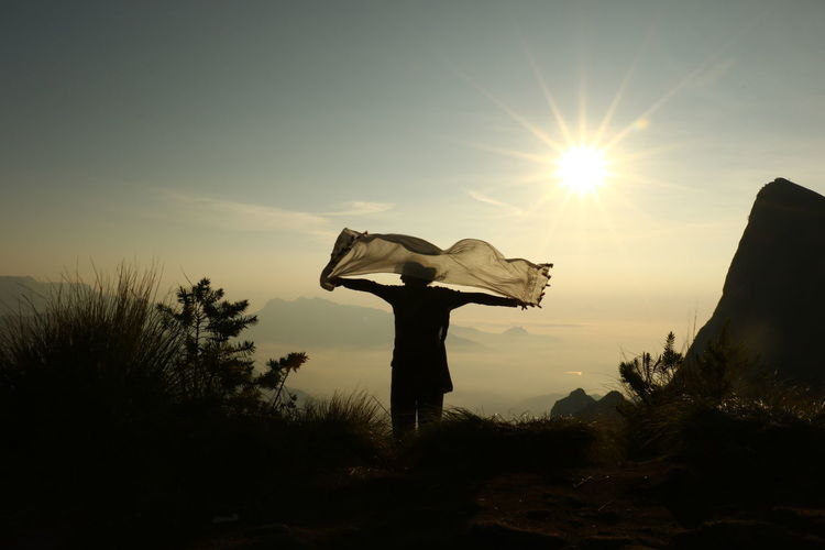 Silhouette Woman Holding Scarf While Standing Against Sky During Sunset