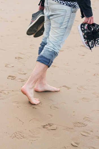 Low section of man walking on beach