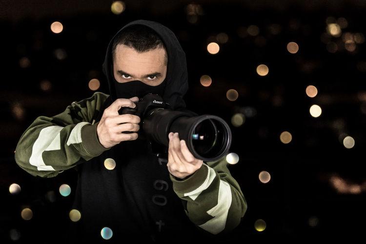 Portrait of man holding camera at night