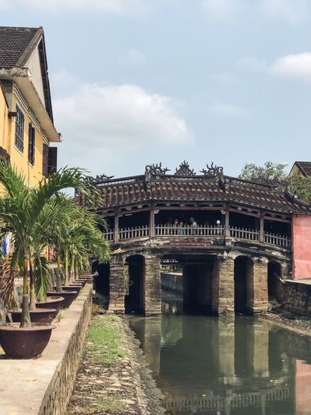History Architecture Vietnamese Japanese Traditional Japanese Style Pedestrian Bridge Covered Bridge UNESCO World Heritage Site Cultural Heritage Tourist Attraction  Travel Destinations Hoi An Ancient Town Yellow Wall Wall - Building Feature Reflections In The Water Reflection Old Bridge Japanese Bridge History Historical Place Perfume River  Architecture Built Structure Building Exterior Sky Cloud - Sky Day Outdoors Water Tree