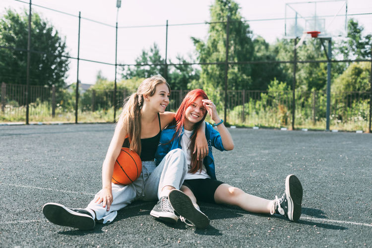 Two girls in sports clothes and with a basketball are chatting, sitting on the playground.