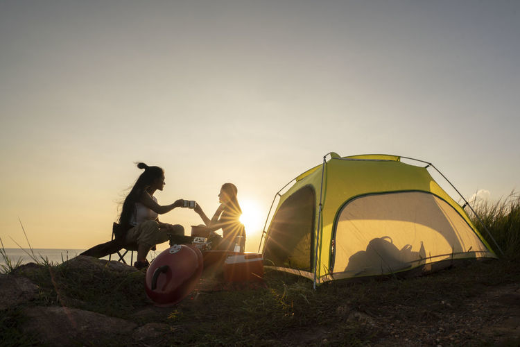 People sitting in tent against sky during sunset