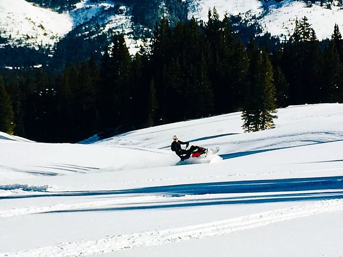 Person riding motorcycle on snow covered mountain