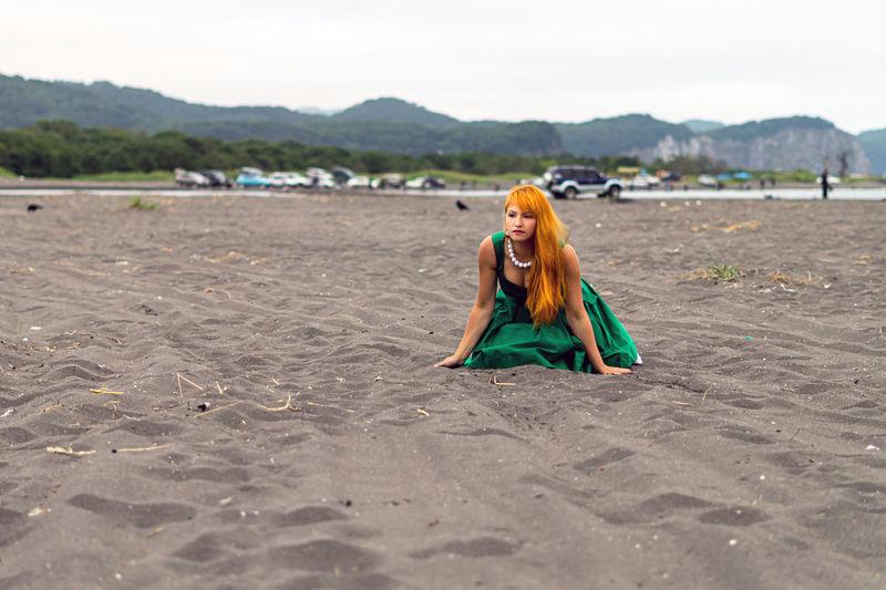 Beautiful woman kneeling at beach
