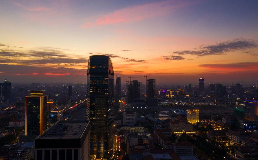 Illuminated modern buildings against sky during sunset