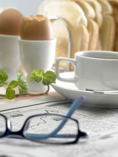 Close-up of coffee cup with newspaper on table