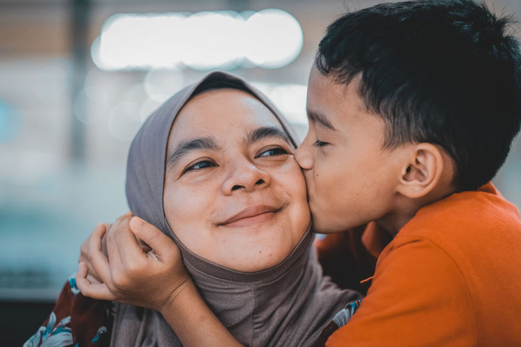 Cute boy kissing mother on cheek at home