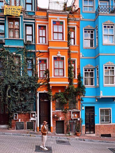 Woman on sidewalk by building in city