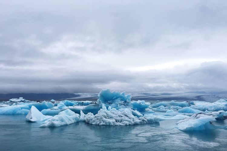 Scenic view of glacier in frozen lake against cloudy sky