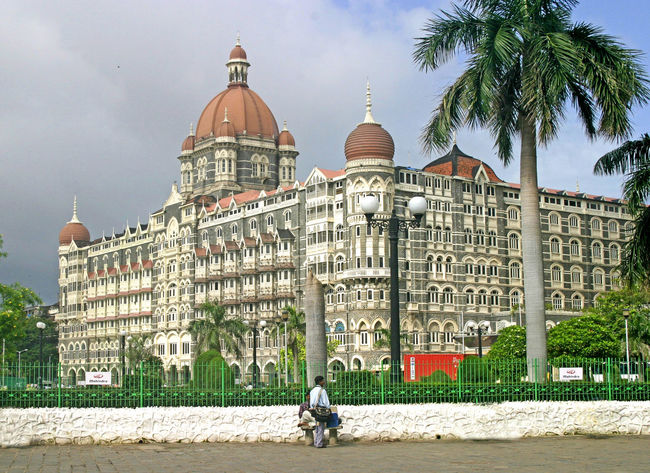 The luxurious Taj Hotel - Mumbai, India BritishRaj Indian Hotels Mumbai, India Taj Hotel Mumbai Domes On Roof Indian Subcontinent Indiapictures Man Looking Palm Trees Breathing Space