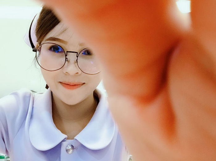 Nurse Nurse Beautiful Woman Close-up Eyeglasses  Females Front View Glasses Headshot Indoors  Leisure Activity Lifestyles Looking At Camera Mid Adult Women One Person Portrait Real People Smiling Women Young Adult Young Women