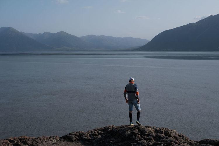 Full length of man standing on rock against sky