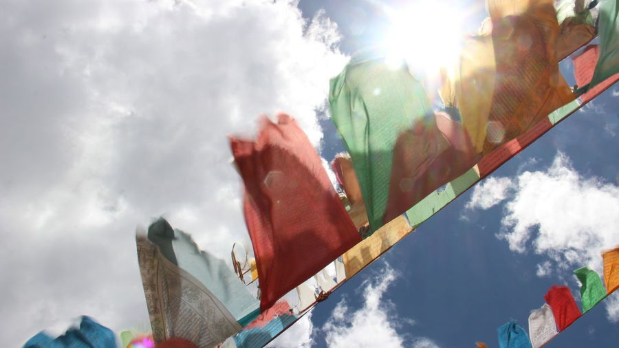 Low angle view of flags hanging against sky on sunny day