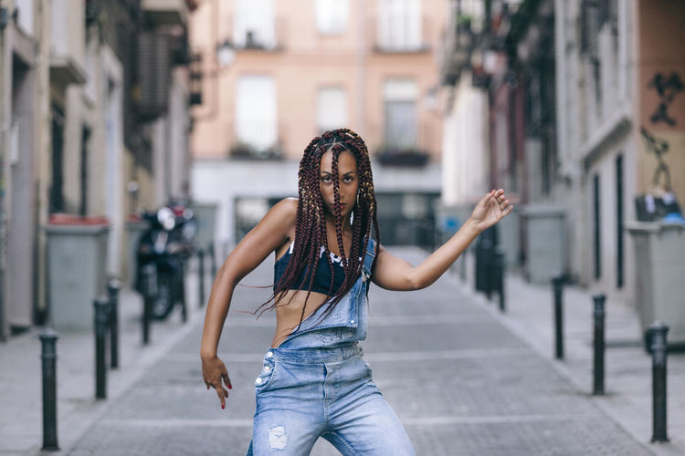 Portrait of woman dancing on street against building