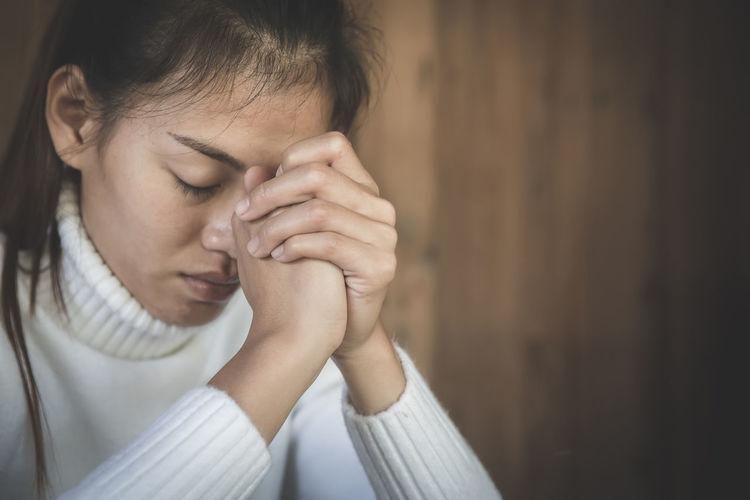 Close-up of young woman praying at church