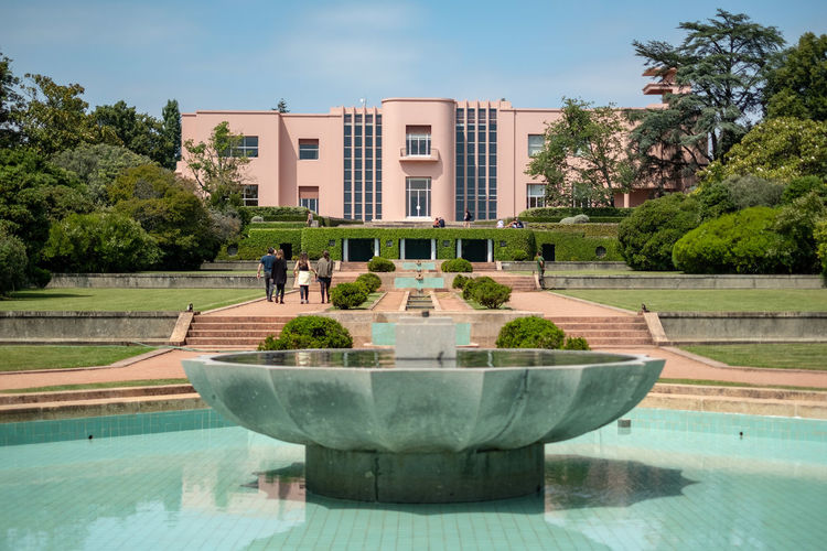 Plant Architecture Built Structure Building Exterior Tree Nature Water Pool Day Fountain Sky Reflection Outdoors Travel Destinations Waterfront Luxury Art Deco Architecture Art Deco Style Art Deco Building Pink Color Pink Plaster Ostentatious Modern