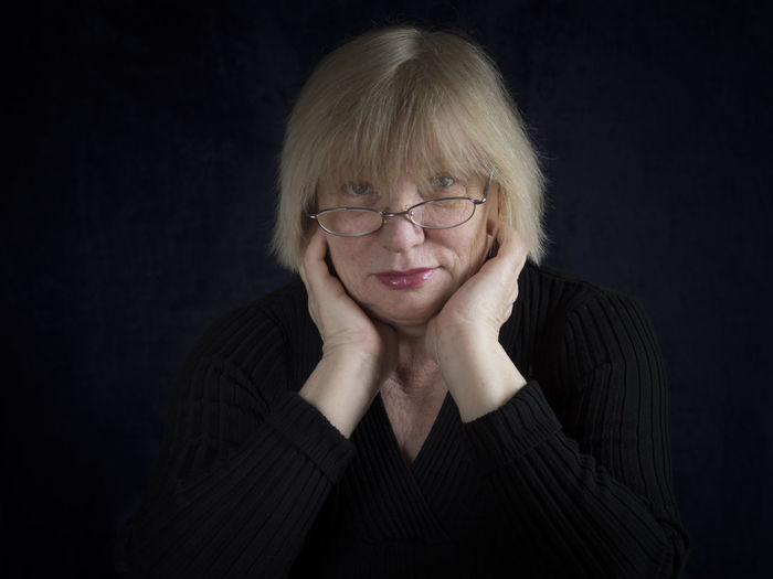 Portrait of mature woman with hands on cheeks against black background