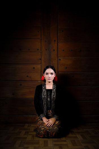 Portrait of woman sitting on wooden floor