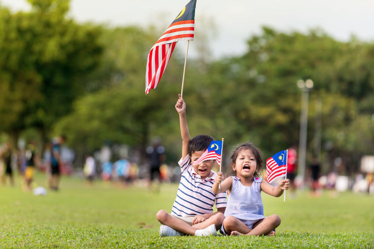 Cute kids playing with flags against trees