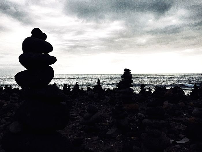 Silhouette stack of rocks on beach against sky