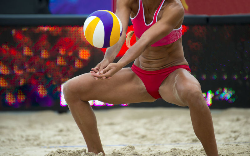 Midsection of woman playing volleyball in stadium