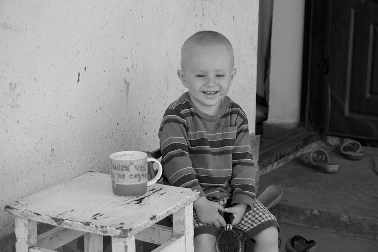 Boy smiling while sitting at table against wall
