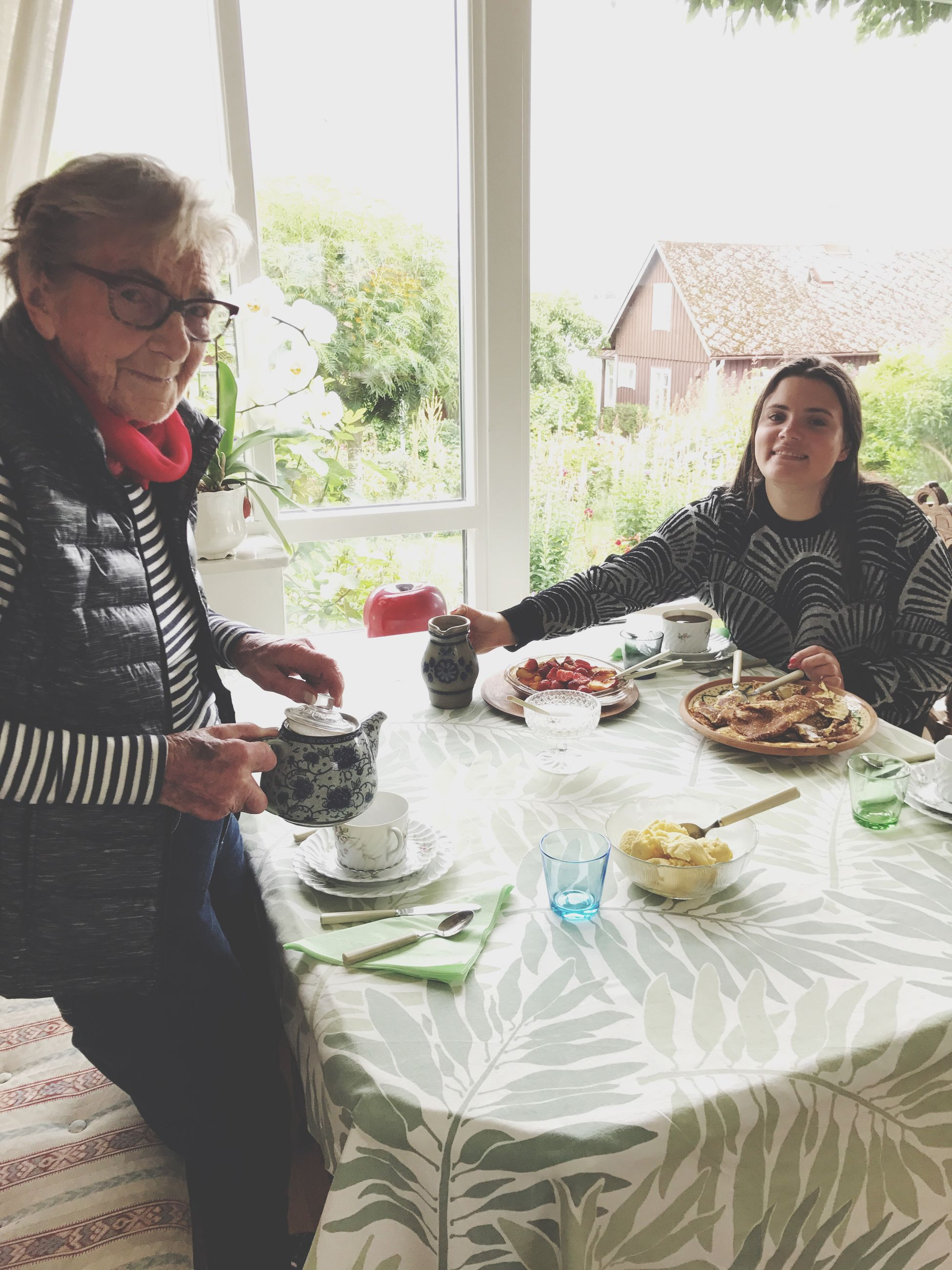 table, two people, food and drink, senior women, window, sitting, senior adult, home interior, togetherness, indoors, lifestyles, food, eyeglasses, casual clothing, real people, day, drink, plate, domestic life, friendship