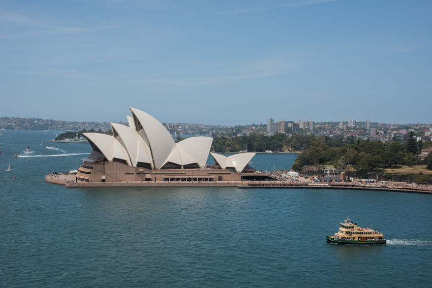 Sydney,NSW,Australia-November 20,2016: Elevated view over the Sydney Opera House at Bennelong Point in Sydney, Australia 20th Century Architecture Australia Cityscape Harbour Roof Royal Botanic Gardens Sydney Cove Sydney Opera House Tourist Tourist Attraction  Transportation Venue Arts Culture And Entertainment Bennelong Point Boat Expressionist Farm Cove High Angle View Landmark Nautical Vessel Sydney Travel Destinations Wake Water