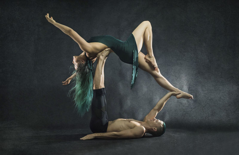 Full length of couple performing modern dance against gray background