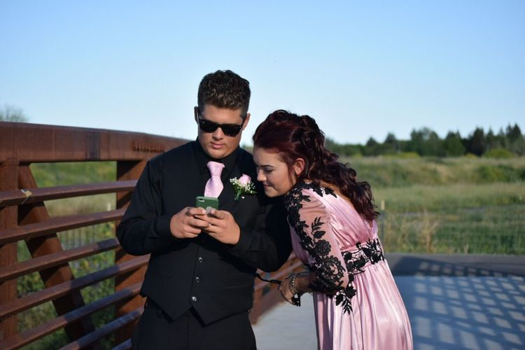 Smiling couple looking at smart phone while standing against clear sky