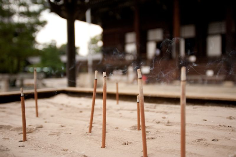 Incense Sticks In Sand Outside Temple