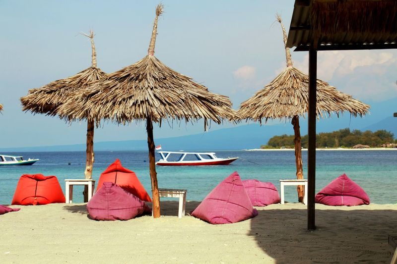 Lounge chairs and umbrellas on beach against sky