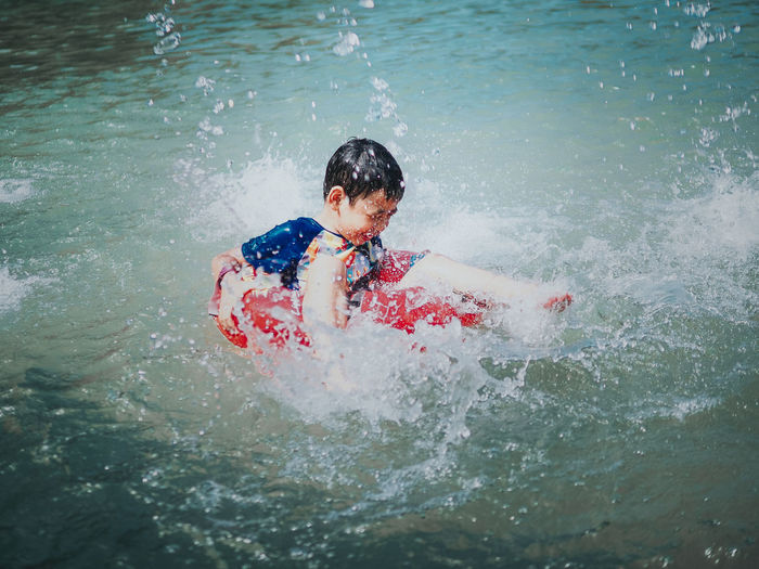 High Angle View Of Boy Sitting On Inflatable Ring At Lake