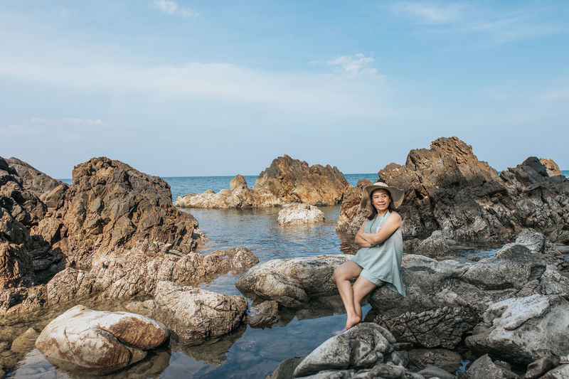 Portrait of young woman on rock against sea